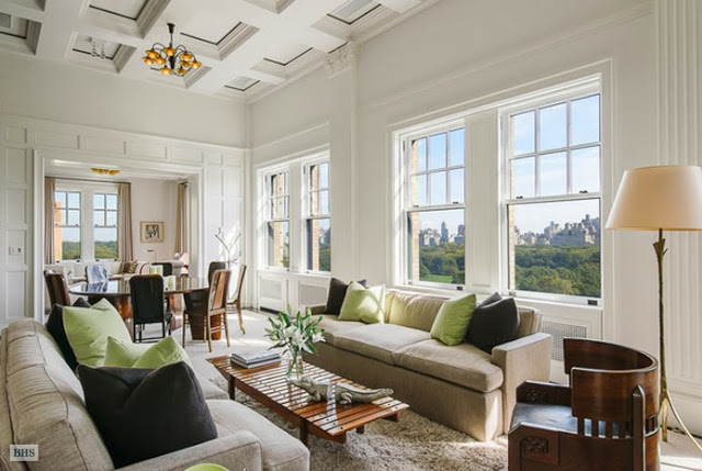 Living room in a New York penthouse with dueling sofas, a shag rug, large windows with a view of Central Park and coffered ceiling