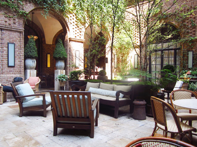 guest courtyard at the The Greenwich Hotel with stone floors, visible brick walls with arched entryways, potted plants and wooden and wicker arm chairs, tables and benches