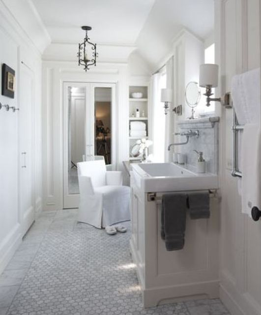 White bathroom with farmhouse style sink, a wall mounted faucet, marble hexagon Carrara marble tiles on the floor, a white armchair and a pair of white slippers