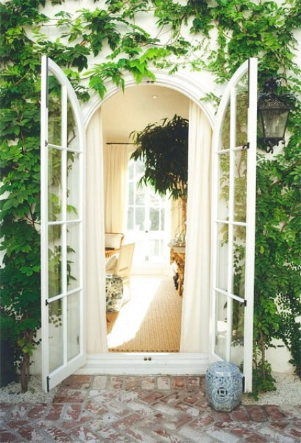 Wall covered in ivy with arched French doors leading inside propped open with a porcelain Chinese garden stooll