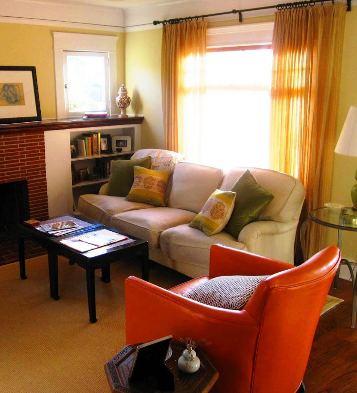 Grey sofa in a living room with green and yellow accent pillows. The living room has a sea grass rug, two black tables smushed together to function as a coffee table and an orange leather armchair