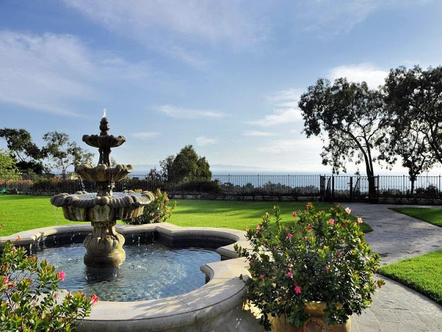 Ocean view from the backyard with a traditional fountain, a lawn and potted plants