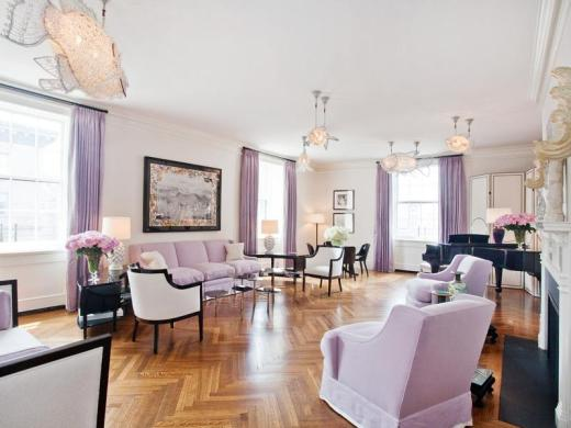 lavendar living room in a Park Avenue Apartment with herringbone wood floors, crystal fish light fixtures, lavender curtains with a matching sofa and upholstered armchairs, a baby grand piano and a fireplace