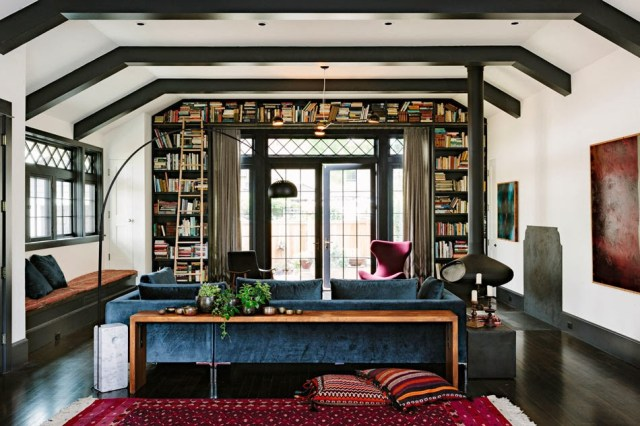 Living room with dark wood floor, exposed ceiling beams and blue sofa