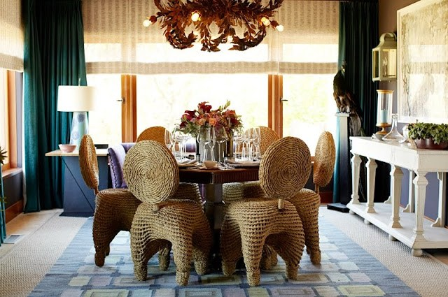 dining room with wicker chairs surroudning a wood table with a flower arrangement, a chandelier with branches covered in leaves and floor length turquoise curtains