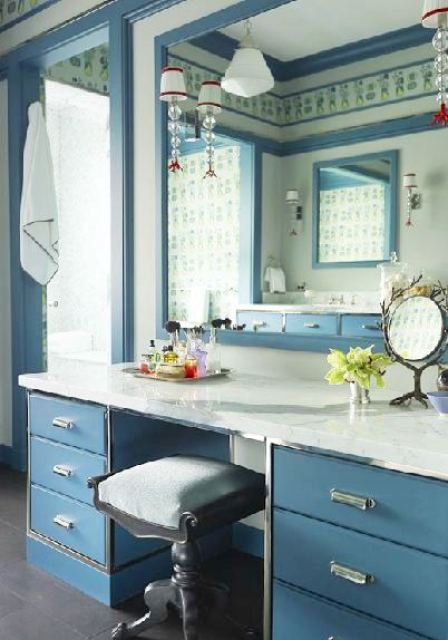Vanity in a master bathroom with blue cabinets, marble counters, and a stool with a blue velvet cushion