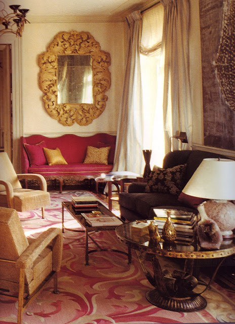 Formal living room with two rope armchairs, a pink Louis XIV armchair under a large antique mirror, a brown sofa in front of a small coffee table with a large glass round table on the side