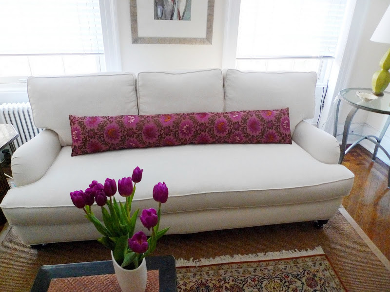Light grey sofa in a living room with a long pink flower printed pillow on a sea grass rug