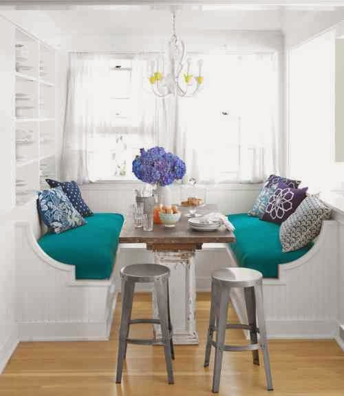 Breakfast nook with built in benches, a white chandelier and metal stools