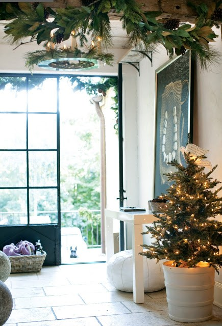 Foyer with small Christmas tree, white Moroccan pouf and a tile floor
