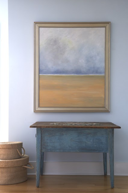 Painted wood console table with a painting hanging on a blue grey wall