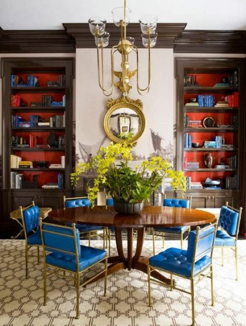 Dining room with built in shelves and vintage chairs with blue upholstery