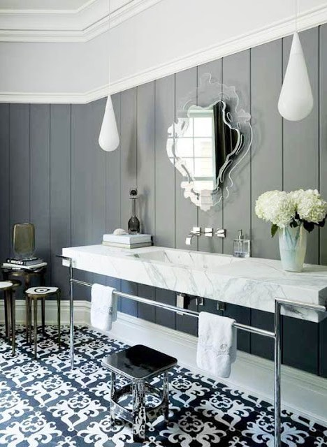Bathroom with black and white Moroccan inspired tile floor, teardrop lighting, gray wood planked walls, a wall mounted sink with long marble counter, a mirror with a Lucite frame and a silver stool