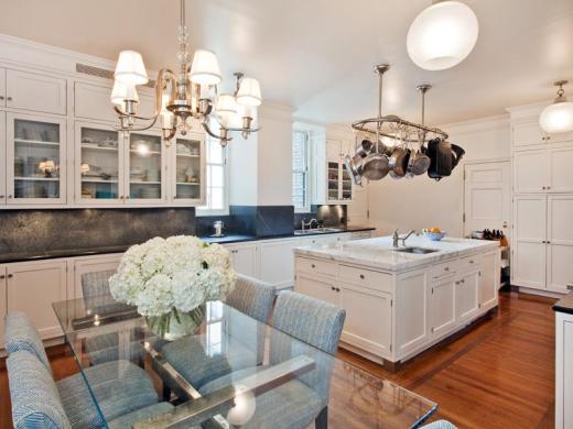 Eat in kitchen in a park avenue apartment with white cabinets, a pot rack hanging over an  island with marble countertop, wood floors, and a glass table surrounded by blue upholstered seats with a chandelier above it