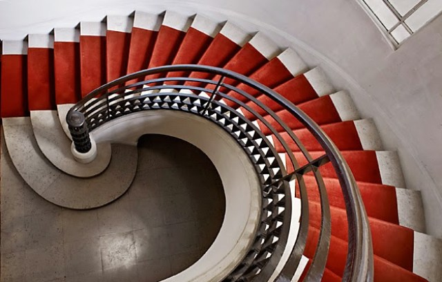 Spiral staircase with metal banister and red carpet