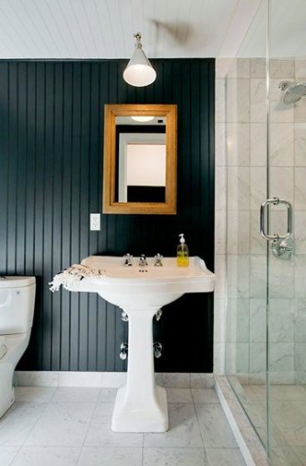 Bathroom with black beadboard walls, a pedestal sink, marble tile floor, a single pendant light and a mirror in a wood frame