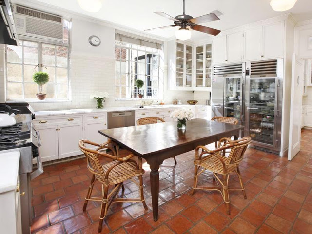 kitchen in an apartment with Saltillo tiled floors, traditional white cabinetry, subway tile backsplash, stainless appliances and glass front refrigerator.