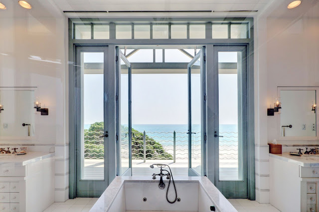 ocean view from the white master bathroom with stand alone bathtub facing blue trimmed glass doors and windows lead onto a balcony.