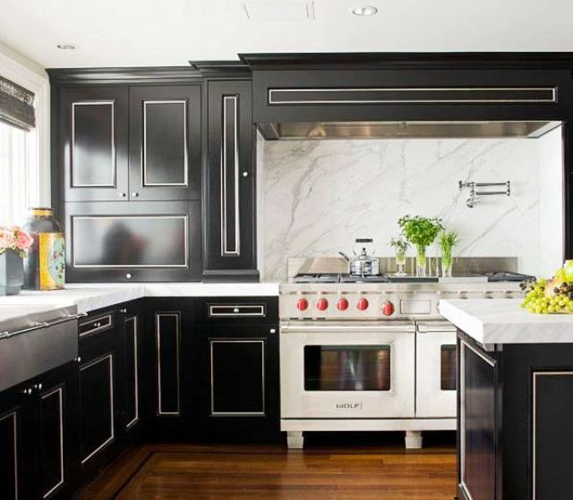 kitchen with black cabinets with white trim, wolf range stove and oven, and marble slab backsplash