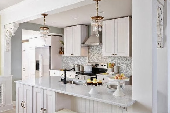 Bright, white kitchen after makeover with stainless appliances and mosaic tile backsplash