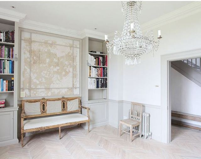 Foyer with herringbone wood floor, crystal chandelier, a bench and built in bookshelves