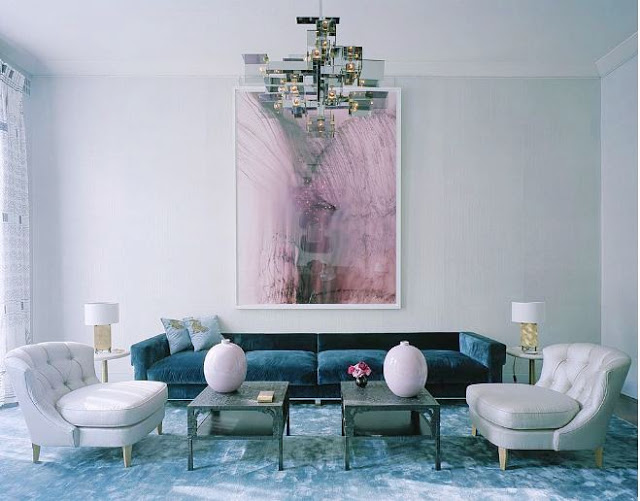 Living room in london with a blue velvet sofa, light grey tufted armchairs, two small coffe tables, a modern chandelier and a pink piece of modern art on the wall