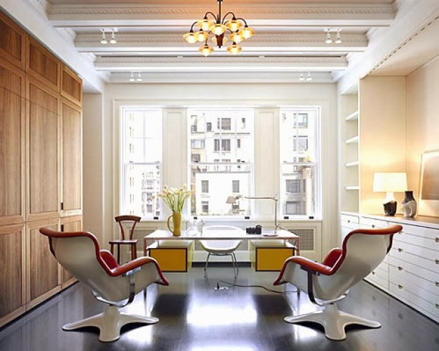 Home office in a New York City penthouse with modern furniture, dark wood floor, coffered ceiling and built in shelving