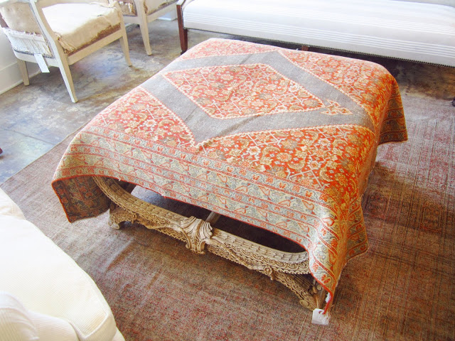 Vintage fabric is draped over a stunning carved ottoman