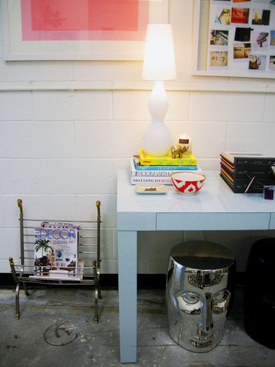 Office with a  light blue glossy Parsons Desk, a silver garden stool and vintage magazine rack