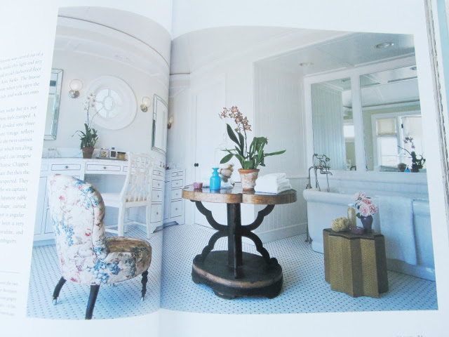 Bathroom in book by Kitchens and Baths by Michael S. Smith with a white stand alone tub, upholstered flower print arm chair, white vanity with gold drawer pulls, and a table