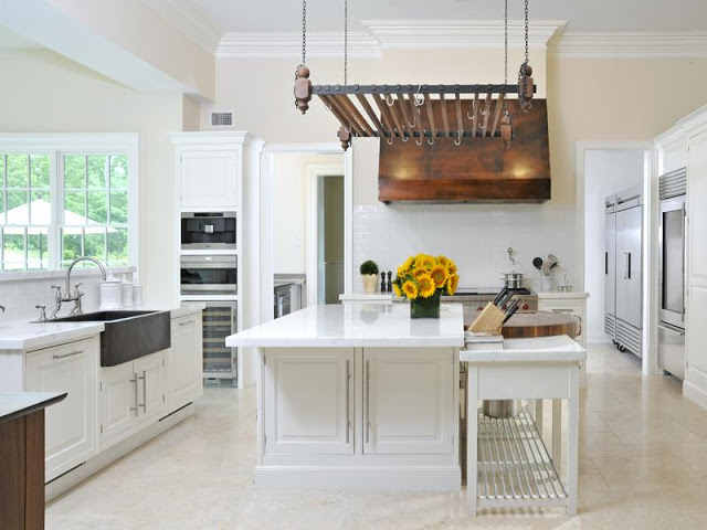alternative view of the white kitchen with view of copper hood and farmhouse sin