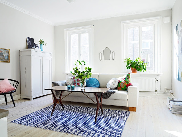 Living room in a tiny apartment with light wood floors, neutral light gray walls, white furnishings, a grey sofa with a wood coffee table and a bright blue and white rug