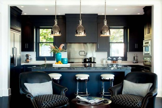 Kitchen with dark blue cabinets, white backsplash, black and white barstools at a dark blue island, stainless appliances and three silver pendant lights
