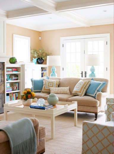 Living room in a cottage with coffered ceiling, camels walls and sofa, bamboo floor, built in book shelves, french doors and matching camel trellis armchairs