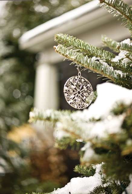 Close up of an elegant, silver Christmas oranment hanging from a tree covered in snow