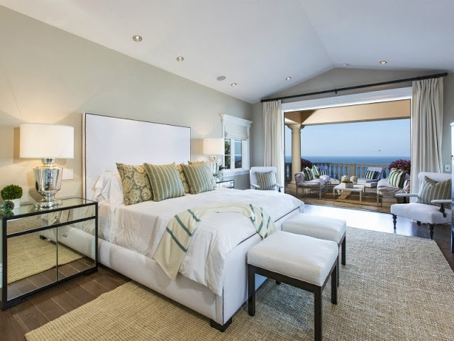 Bedroom in a Malibu villa with mirrored night stand and lamp and tall white headboard