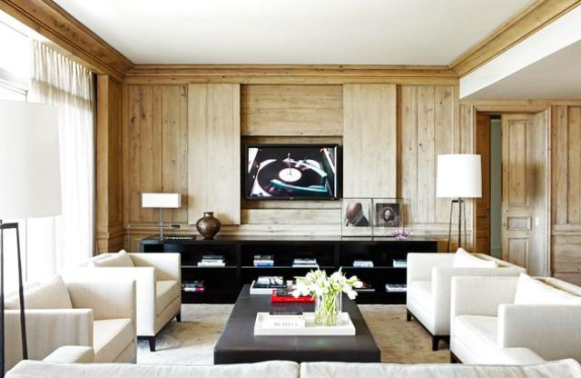 Modern family room with dueling white armchairs, a long dark ottoman being used as a coffee table, black book shelves and light wood paneling concealing a television