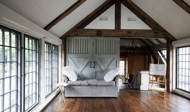 Yoga studio with hardwood floors, large paned windows, exposed beams, and a sliding barn door