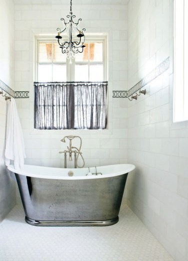 Bathroom with tile walls and an accent stripe, a window with sheer black curtains, a chandelier and a silver stand alone bathtub