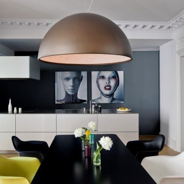 marie claire maison dining room with  oversized dome pendant light, large black, white and yellow eames chairs and dark walls