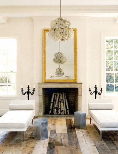 Living room with dueling sofas, reclaimed wood floors, fireplace with a large traditional gold mirror on the mantel