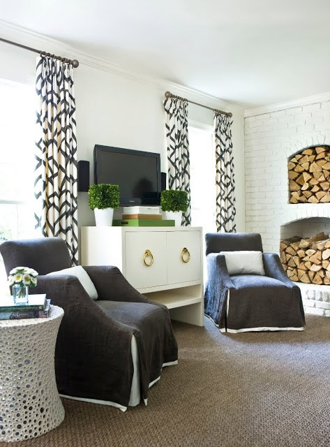 Living room with white lacquer cabinet with brass pulls serving as a television cabinet and two armchairs with layered slipcovers