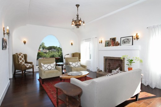 White living room with arched window, club chairs and a grey sofa with cococozy pillows and throws, dark wood floors, a red Moroccan rug, a brick fireplace and a chandelier