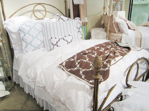 COCOCOZY throw, shams and boudoir pillows on an elegant white Downtown Company duvet cover in the Christian Mosso & Associates Showroom in Atlant