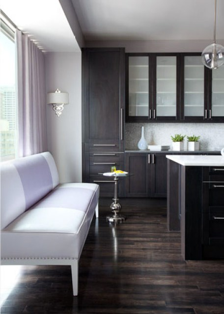 Alternative view of the kitchen with dark wood floors and cabinets from floor to ceiling. In this view you can see the picture window with lavender floor length curtains and a long lavender upholstered bench with nail head trim