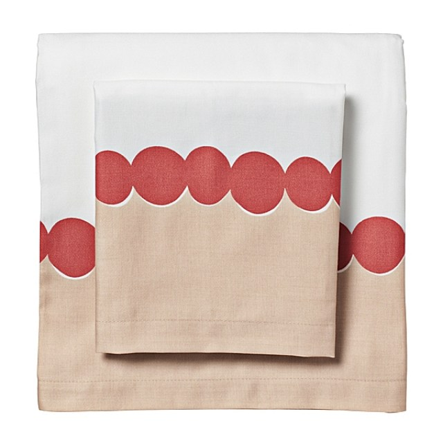 Bed sheets with a light brown bottom and white top separated at the half way point by a row of red dots