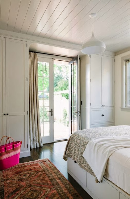 White bedroom with wood floor and French doors