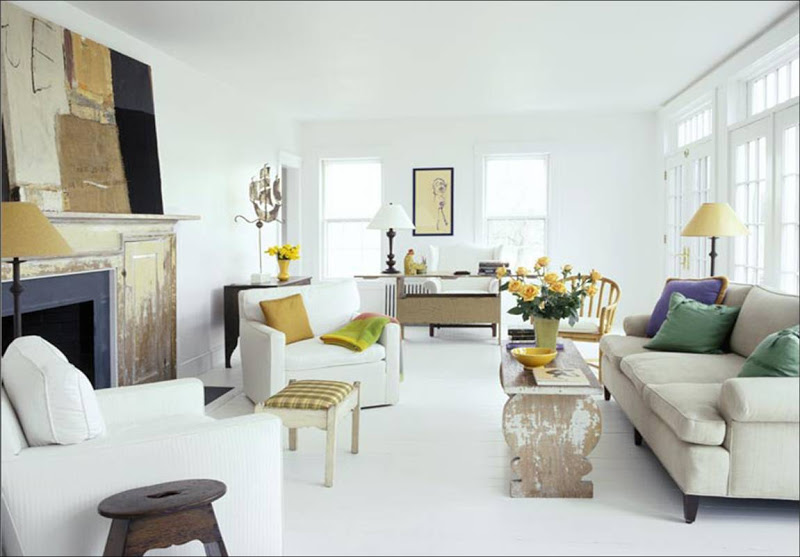 White living room with yellow lampshade, accent pillows and upholstered ottoman