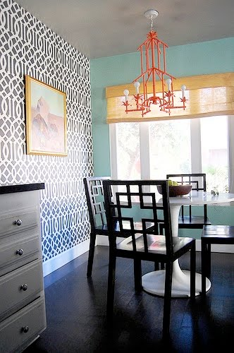 Small dining room with Schumacher's Kelly Wearstler Imperial Trellis wallpaper, a red tole pagoda chandelier, Saarinen white round table and modern dining chairs