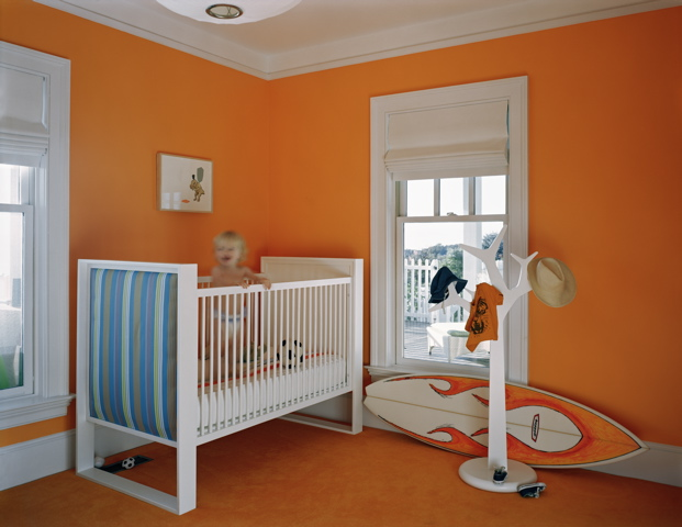 Orange nursery by Ghislaine Vinas with a white crib and a surfboard